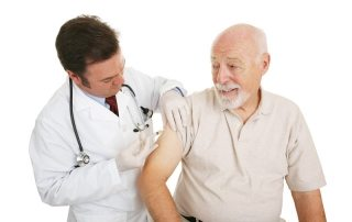 Elderly man getting a vaccine shot as a result of his home care services. .